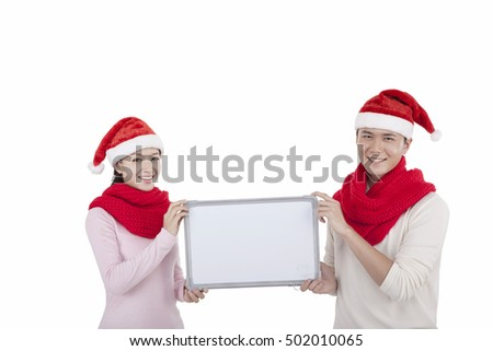 Portrait of young couple wearing Santa hats,holding whiteboard