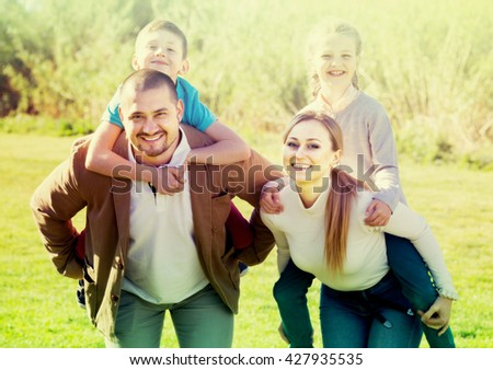 Portrait of young family of four people, mom and dad holding a girl and a boy up on the back - stock photo