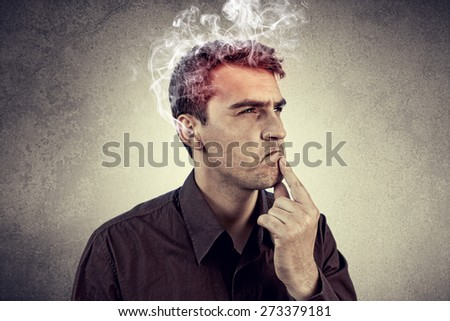 Portrait of Young man intensively thinking too hard with waving smoke from head. - stock photo