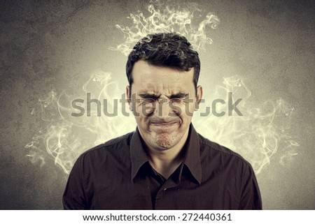 Portrait of Young man thinking too hard .Angry,Stressed man with waving smoke from head. - stock photo