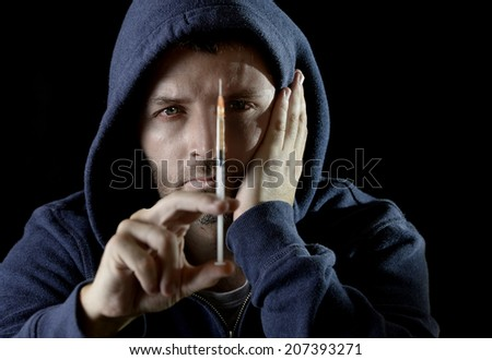 portrait of young sick drug addict man wearing hood holding heroin or cocaine syringe thinking and  looking wasted and depressed facing dope abuse and addiction  - stock photo