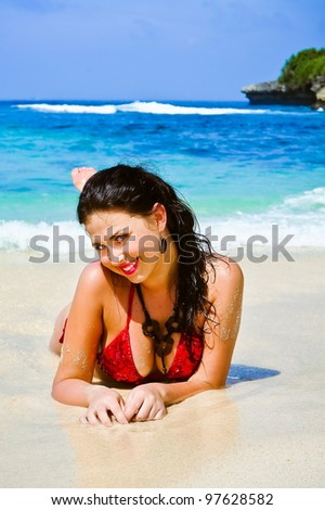 Portrait of young woman lying on beach - stock photo