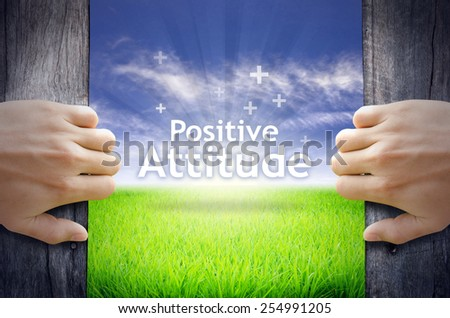 """""""Positive Attitude"""" Motivational quotes. Hands opening a wooden door then found a texts floating among new world as green grass field, Blue sky and the Sunrise. - stock photo"""