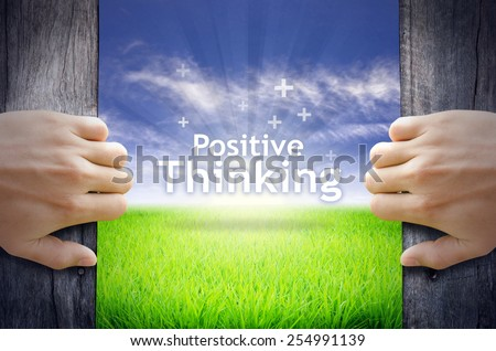 """""""Positive Thinking"""" Motivational quotes. Hands opening a wooden door then found a texts floating among new world as green grass field, Blue sky and the Sunrise. - stock photo"""