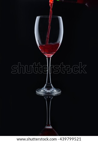 Pour the red wine into the glass on a black background . - stock photo