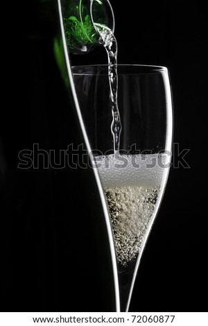 pouring champagne in glass on black background - stock photo