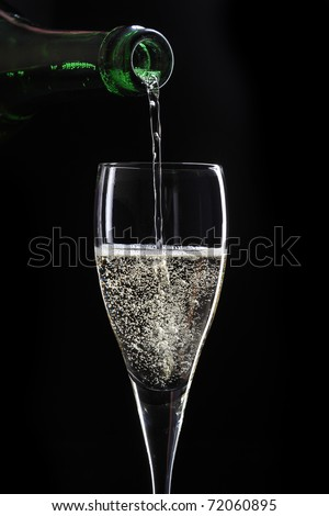 pouring champagne on black background - stock photo