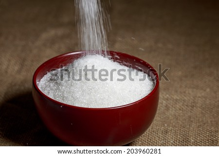 Pouring Granulated Sugar into a wood Bowl - stock photo