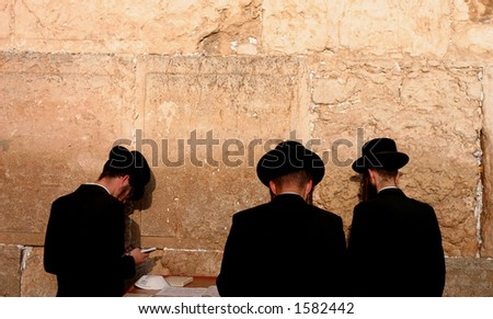 praying by the Western Wall, Jerusalem. - stock photo