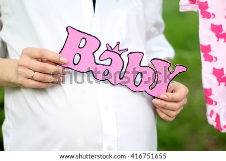 "Pregnancy Concept. Close up of a cute plate with the word ""baby"".  Pregnant woman in the white shirt. - stock photo"