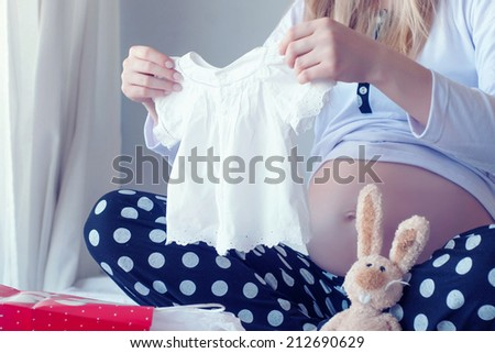pregnant woman holding a  baby dress