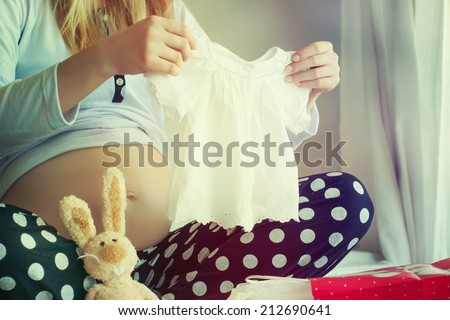 pregnant woman holding a  baby dress  - stock photo