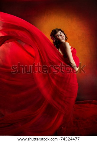 Pregnant woman in red dress waving flying on a wind flow