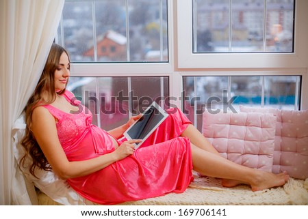 pregnant woman sitting on the window and holding a tablet - stock photo