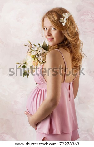 Pregnant woman smiling, looking at camera, holding flowers. Pink dress. - stock photo
