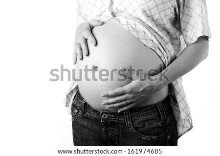 Pregnant woman touching her belly with hands  - stock photo