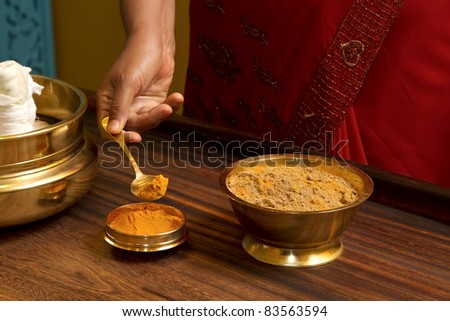 preparing herbs powder for  traditional indian ayurvedic  massage - stock photo
