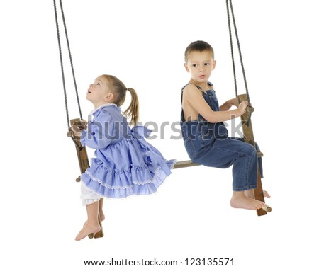 2 preschooler playing on an old wooden, antique 2-person, pump swing together.  The girl is looking up to the top of the ropes, while the brother looks back a bit worried.  On a white background. - stock photo