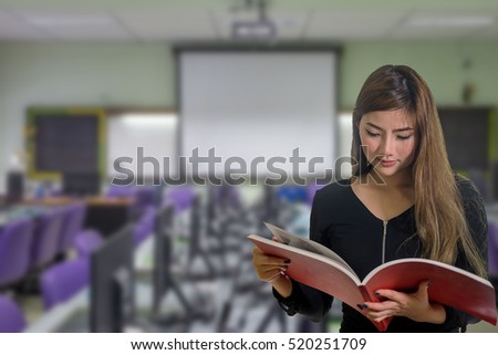 pretty female student with books working in a classroom