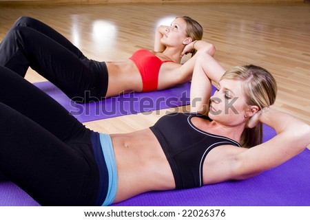 2 pretty girls working out in a gym - stock photo