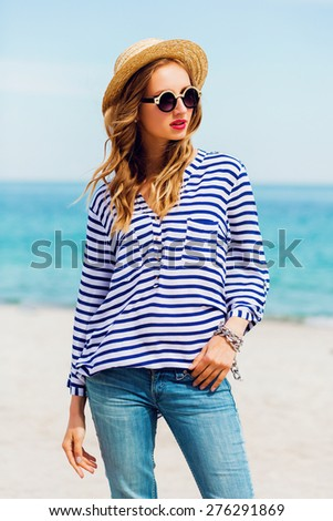 Pretty slim tan  blonde stylish woman in straw hat  and sunglasses. posing on the paradise tropical beach. Have bright mace up and wearing striped shirt.   - stock photo