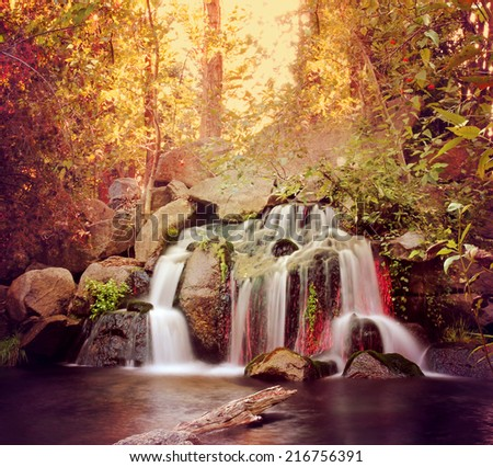 pretty waterfalls toned with a warm filter (slow shutterspeed for cascading water softening) - stock photo