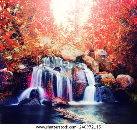 pretty waterfalls toned with a warm retro vintage instagram filter effect (slow shutterspeed for cascading water softening)  - stock photo