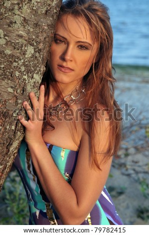 pretty young woman posing at the beach with windswept hair - stock photo