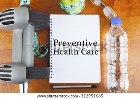 """Preventive Health Care"" text on notebook with green apple, measure tape, spectacle, a bottle of mineral water, and bodybuilding tools on wooden background - healthy, exercise and diet concept - stock photo"