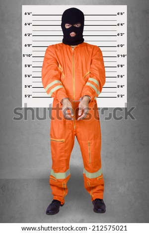 Prisoner with handcuffs standing wearing a balaclava camouflage face in jail against gray police lineup or mug shot background of a death penalty - stock photo