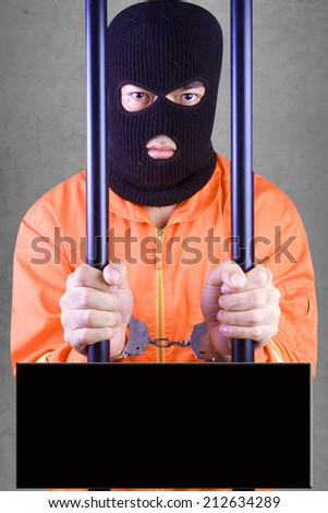 Prisoner with handcuffs wearing a balaclava camouflage face in jail of a death penalty with black blank banner against concrete wall background  - stock photo