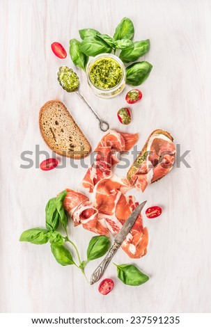 prosciutto ham with toast bread,basil pesto and tomatoes on white wooden background,top view - stock photo