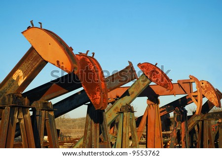 Pump jacks are for sale in a used equipment yard. - stock photo