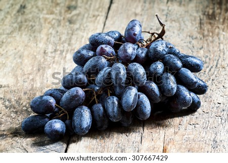 Purple wine grapes on old wooden table, selective focus