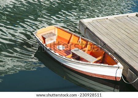 Quaint dinghy, white and orange, tied to floating pier in Boothbay Harbor. - stock photo