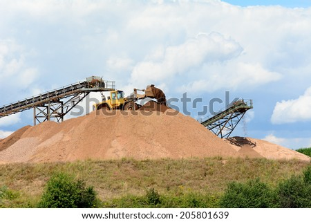 Quarrying work - building stone piles with machinery - stock photo