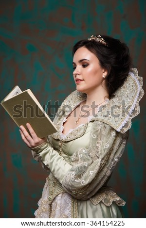 queen in royal dress.queen in royal dress reading a book. actress with an old dress - stock photo