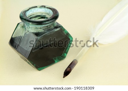 Quill pen and glass ink bottle  on paper - stock photo