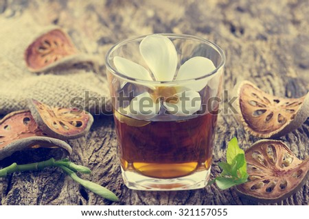 Quince water in glass with dried quince on wooden, Infused detox water - stock photo