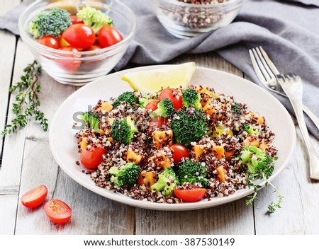 Quinoa salad with broccoli,sweet potatoes and tomatoes on a rustic wooden table.Superfoods concept.Selective focus. - stock photo