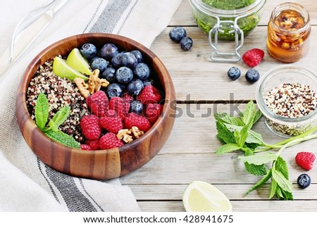 Quinoa salad with fresh raspberries,blueberries,walnuts and mint lime honey dressing.Superfoods and clean eating concept .Selective focus - stock photo