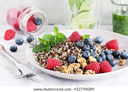 Quinoa salad with fresh raspberries,blueberries,walnuts and mint lime honey dressing.Superfoods and clean eating concept .Selective focus. - stock photo