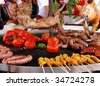 rabbit, meat and vegetables in course of barbecue preparation at spring fair in Barcelona, Spain - stock photo