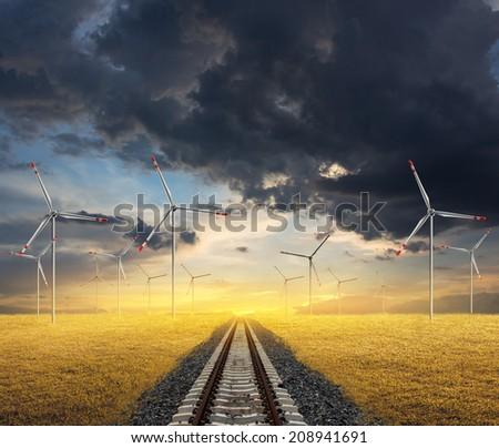railroad with wind turbine on sunset background - stock photo