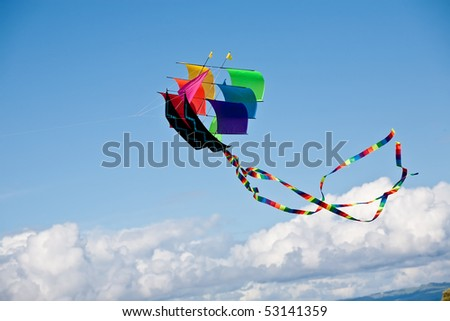 """Rainbow Ship"" kite on sky and clouds background - stock photo"