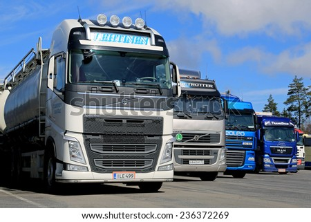 RAISIO, FINLAND - APRIL 12, 2014: Row of trailer trucks parked on a yard. The total transport volume of lorries was 5.4 billion tonne-km in Q2 of 2014, 10% more than in Q2 of 2013.  - stock photo