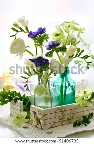 ranunculus, anemone, freesia and hellebore in glass bottles - stock photo