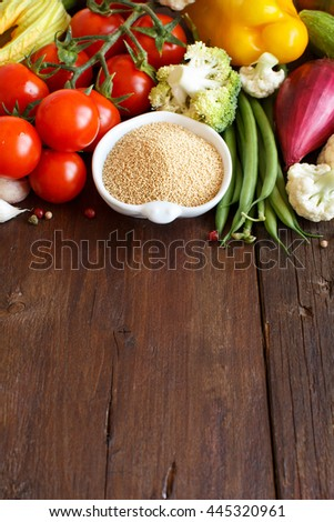 Raw Amaranth Grain in a bowl and vegetables on wood