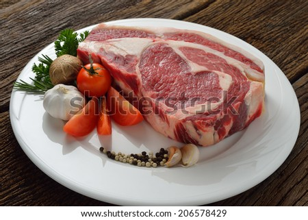 Raw meat ready to be cooked on wooden background ( rib eye steak )                                                                                           - stock photo
