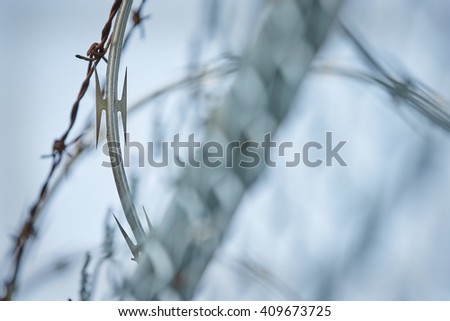 Razor Wire. Razor wire and barbed wire at the top of a fence.                          - stock photo